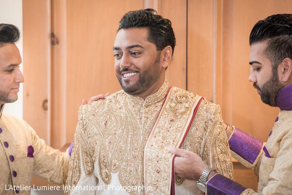 Indian groom being helped by Indian groomsmen.