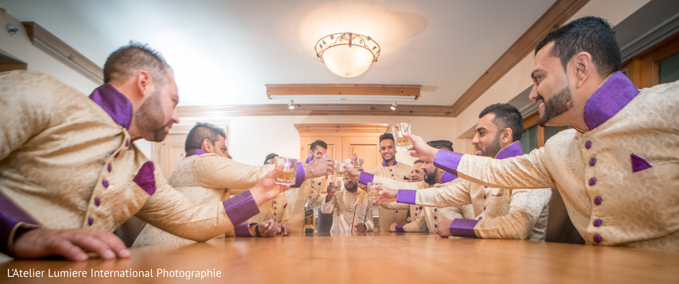 Indian groomsmen and groom having a toast.