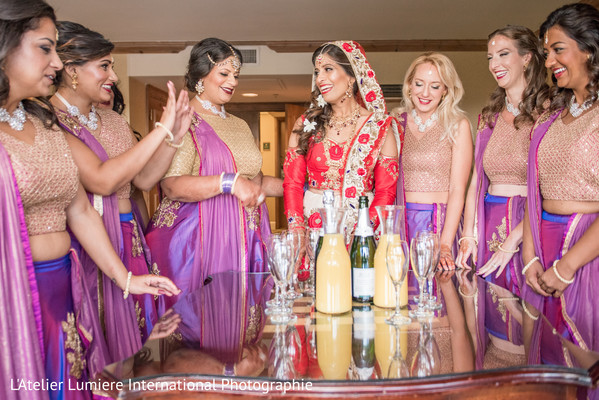 Indian bride with bridesmaids about to have a toast.