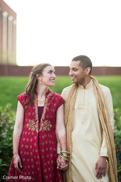 Beautiful Indian couple hold hands as the outdoor photo shoot continues.