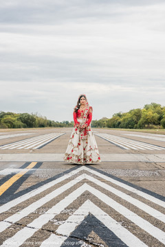 Dreamy Indian bride on her ceremony outfit in an outdoors portrait.