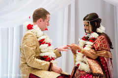 Indian bride putting wedding ring on groom
