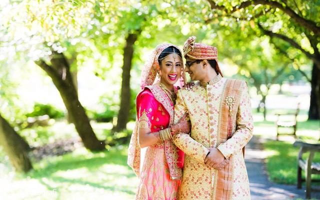 Indian bride and groom pose for pictures during the outdoor photo shoot