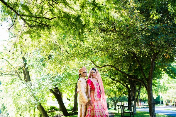 Elegant Indian groom and stunning maharani pose under a tree