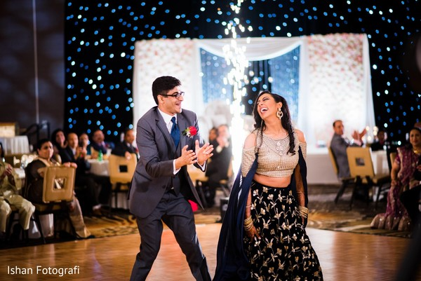 Indian newlyweds have a great time dancing as guests observe and cheer