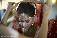 Beautiful Indian bride being assisted with the ghoonghat