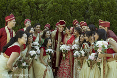 Indian bridesmaids and groomsmen surround the happy Indian couple