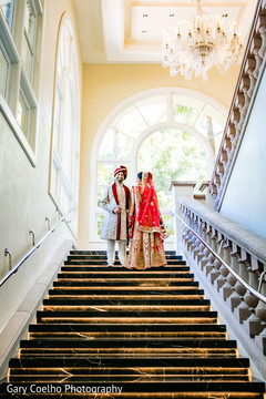 Dreamy portrait of Indian bride and groom standing on the stairs.
