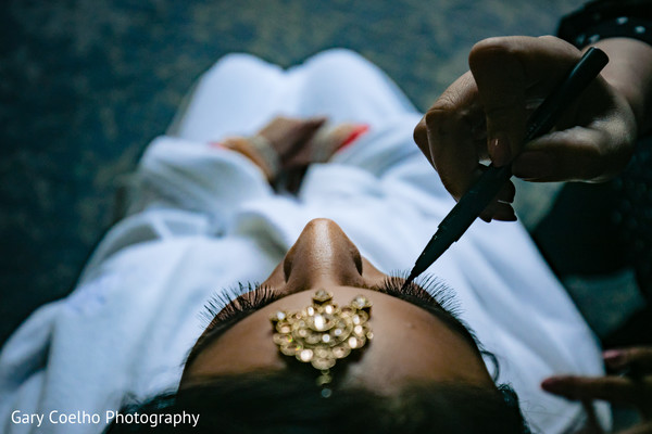 Indian bride getting makeup last touch ups for her wedding ceremony.