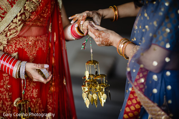 Indian bride getting ready by putting her kalire on.