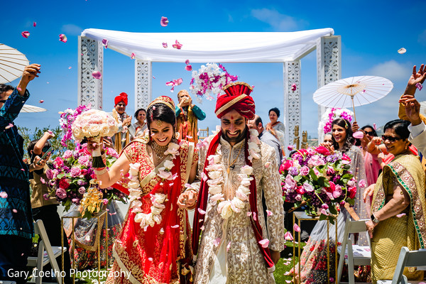 Joyful Indian bride and groom walking out  hand in hand from wedding ceremony.