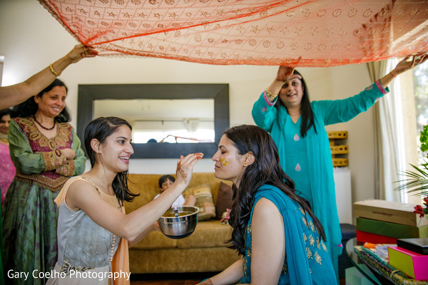 Indian bride getting the haldi paste on.