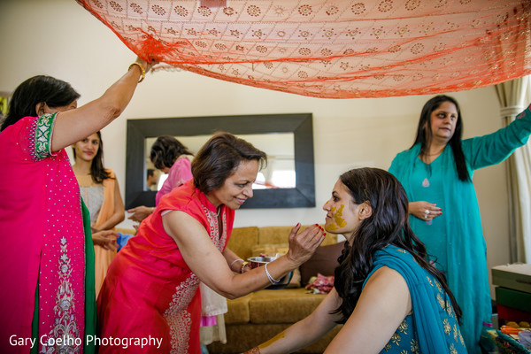 Indian bride getting Turmeric past on.