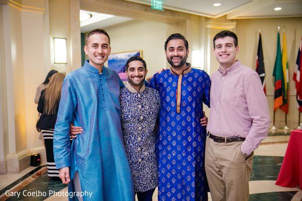 Joyful Indian groom posing  with groomsmen at sangeet celebration.