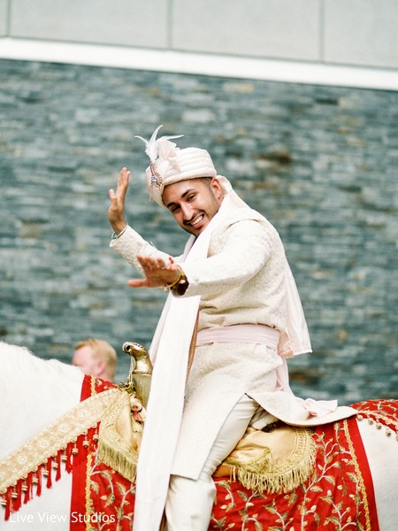 Elegant Indian groom waving during the baraat