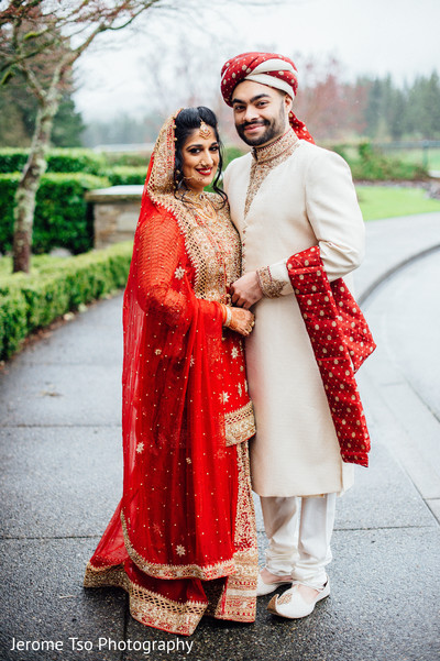 Ravishing Indian bride and groom posing outdoors.