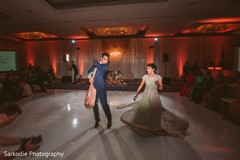 Gorgeous Indian bride and groom at their wedding reception dance performance.