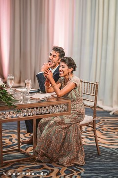 Indian bride and groom capture during reception speech.