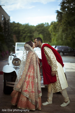 Elegant Indian newlyweds kiss for the outdoors photography