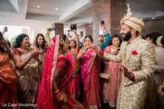 Indian bride and groom dancing during baraat