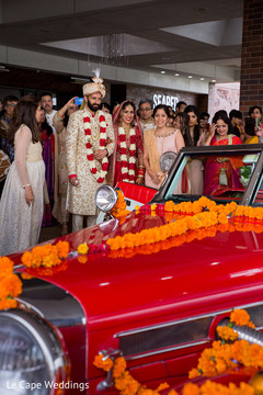 Indian newlyweds stare at the stylish car after the ceremony