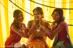 Beautiful shot of the Indian bride and her sisters during the Haldi ceremony