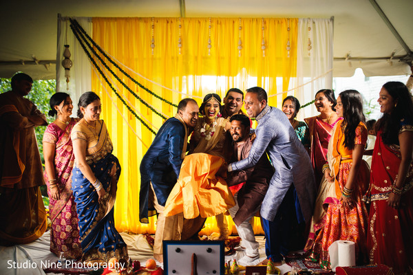 Indian bride is lifted by the special guests during photo shoot