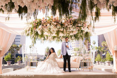 Indian bride and groom hold hands under the floral mandap