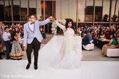 Indian groom escorts the bride down the dance floor