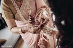 Indian bride getting her Hath Panja bracelet on.