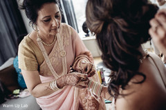 Marvelous Indian bride being helped with Hath Panja bracelet.