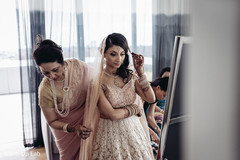 Enchanting Indian bride getting help to put her wedding Ghoonghat veil on.