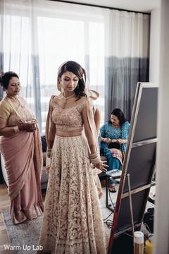 Indian bride admiring her wedding attire capture.