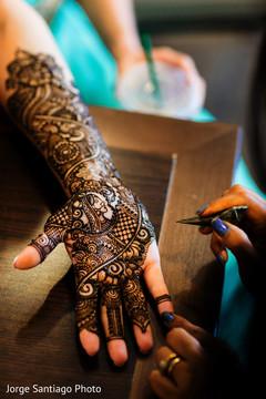 Mehndi artist working on the beautiful design on the maharani