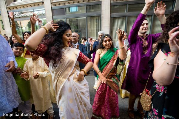 Joyful Indian guests dance during the baraat