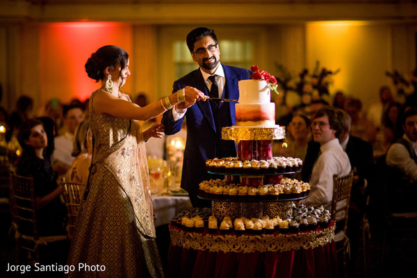 Indian couple cut the wedding cake as guests observe