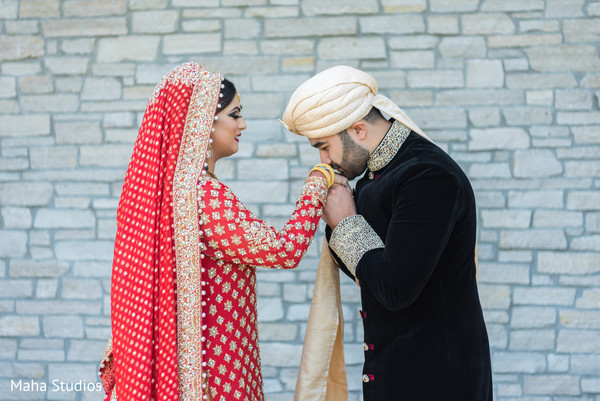 Indian groom kissing the bride's hand