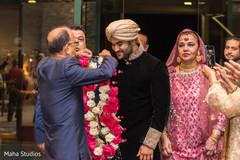 Indian groom receiving garland