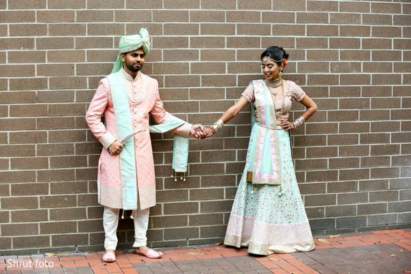Indian bride and groom pose for pictures while holding hands