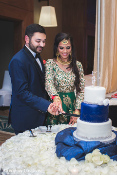 Indian newlyweds cut the wedding cake during the reception