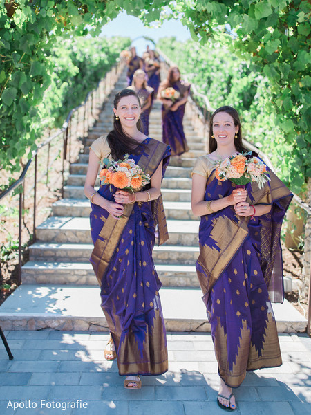 Beautiful bridesmaids holding the flower arrangements entering the ceremony