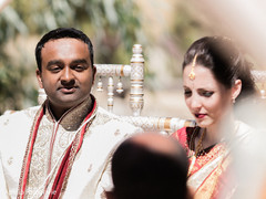 Capture of the Indian couple during the ceremony wearing the sherwani and the sari