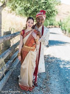Indian newlyweds wearing the traditional wedding clothing outside