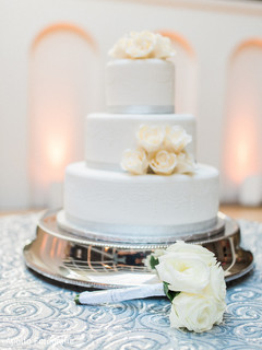 Closeup of Indian bridal bouquet next o wedding cake capture.