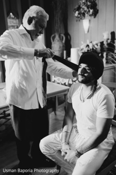 Stunning capture of the Indian groom being aided with his Pagri