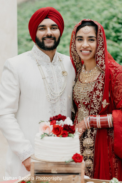 Dazzling portrait of the Indian newlyweds in front of the cake