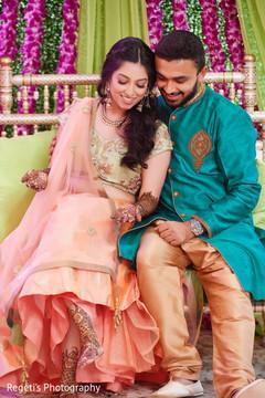 Sweet indian groom looking at bride's mehndi