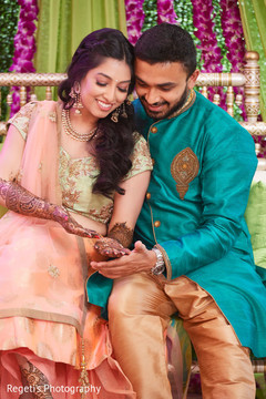 Indian groom admiring mehndi designs