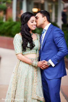 Indian groom sweetly kissing the bride