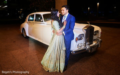 Indian couple posing next to their classic car